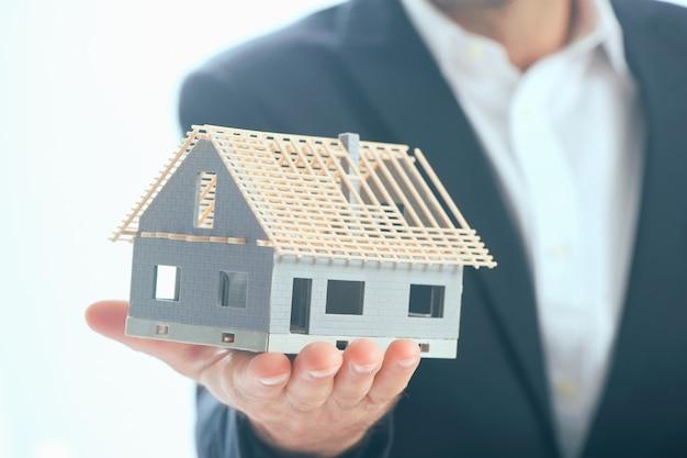 Biznesmen trzymający w dłoniach model domu