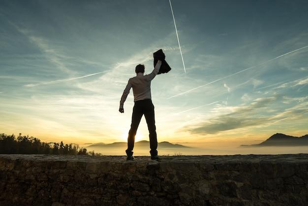 Biznesmen trzymający w górze marynarkę o zachodzie słońca, gdy stoi na ścianie z widokiem na mglistą górską scenę na tle jasnego, kolorowego nieba ze smugami kondensacyjnymi.
