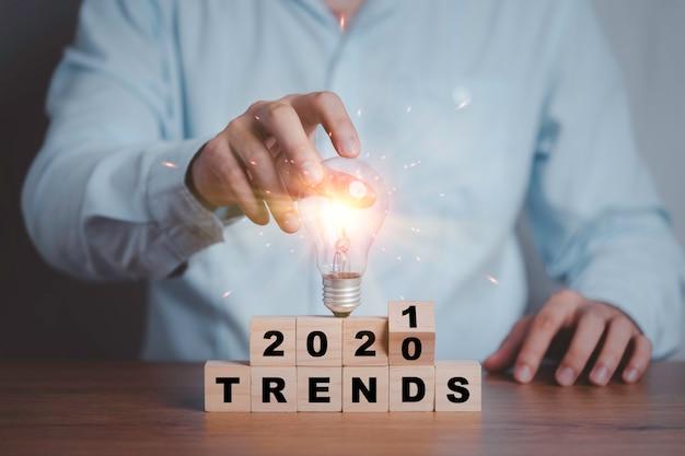 Biznesmen trzymający żarówkę podczas przerzucania trendów z lat 2020-2021, drukując ekran na drewnianych kostkach. nowy pomysł na modę biznesową popularne i istotne tematy.