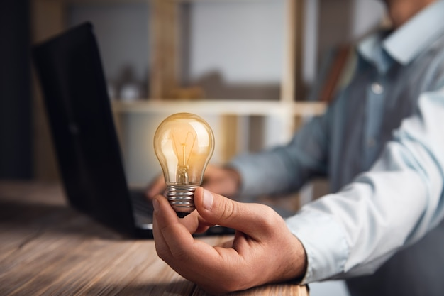 Biznesmen trzymający żarówkę za pomocą laptopa