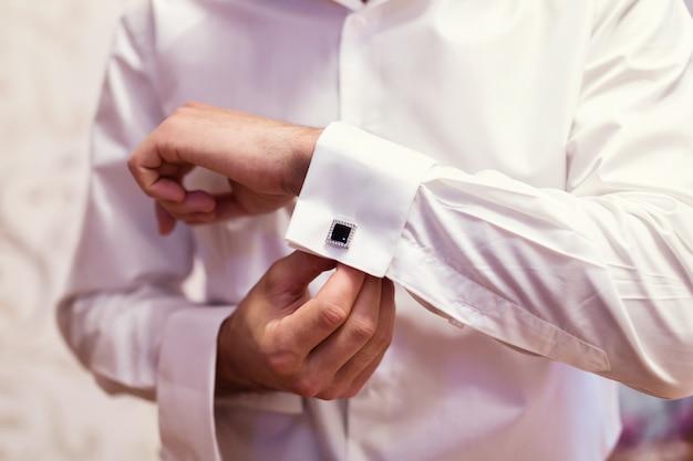 Biznesmen ubiera białą koszulę, męskie dłonie, pan młody przygotowuje się rano przed ślubem,