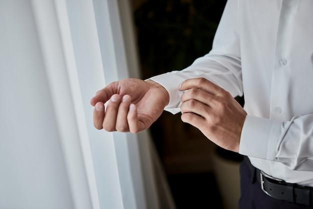 Biznesmen ubiera białą koszulę, zbliżenie męskich rąk, pan młody przygotowuje się rano przed ceremonią ślubną
