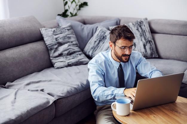 Biznesmen ubrany elegancko siedzi w domu na podłodze i wpisując raport na laptopie.