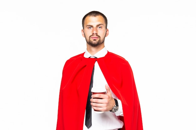 Biznesmen ubrany jak superbohater picia kawy na białym tle