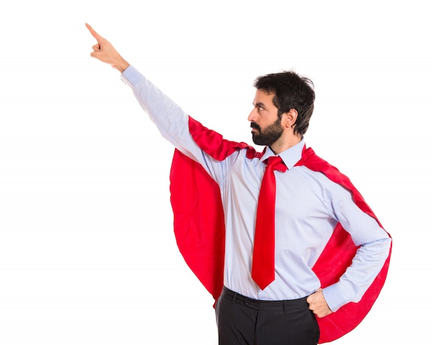 Biznesmen ubrany jak superbohater wskazujący na boczne