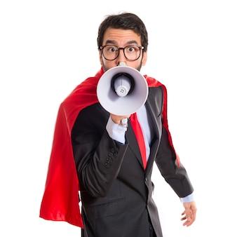Biznesmen ubrany jak superhero krzycząc przez megafon