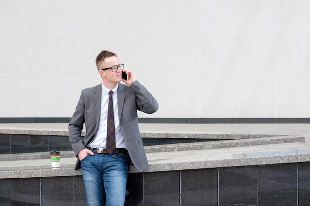 Biznesmen, ubrany w szarą kurtkę, niebieskie dżinsy, białą koszulę i krawat, ma przerwę na lunch w pobliżu centrum biznesu, pije kawę, rozmawia przez telefon