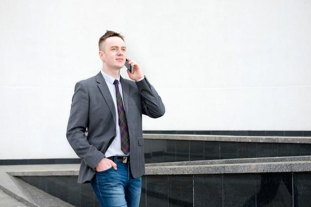 Biznesmen ubrany w szarą marynarkę, niebieskie dżinsy, białą koszulę i krawat wychodzi z centrum biznesowego i rozmawia przez telefon podczas spaceru
