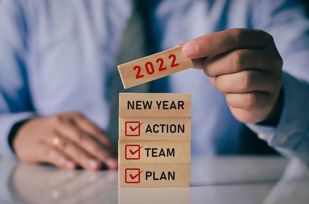 Biznesmen układający drewniane klocki w kolejce nowy rok 2022 pomysł na planowanie biznesu wraz z krokiem