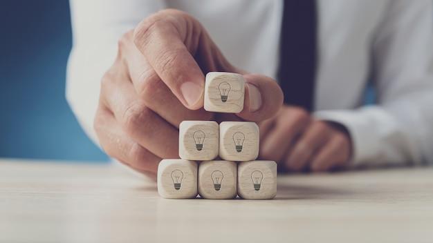 Biznesmen układania drewnianych kostek w kształcie żarówki na nich