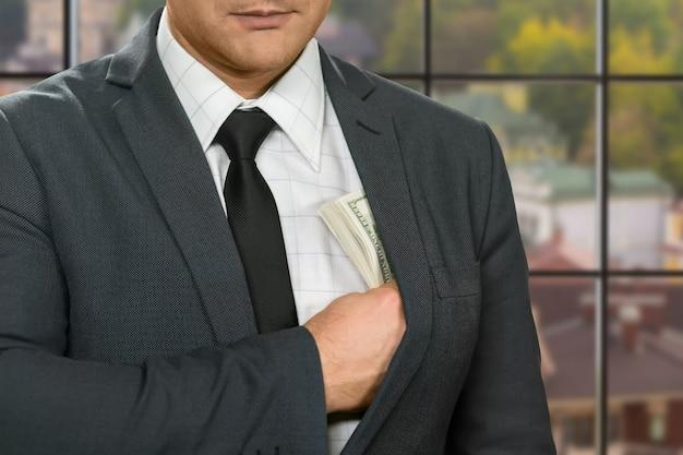 Biznesmen ukrywa dolary w kurtkę.