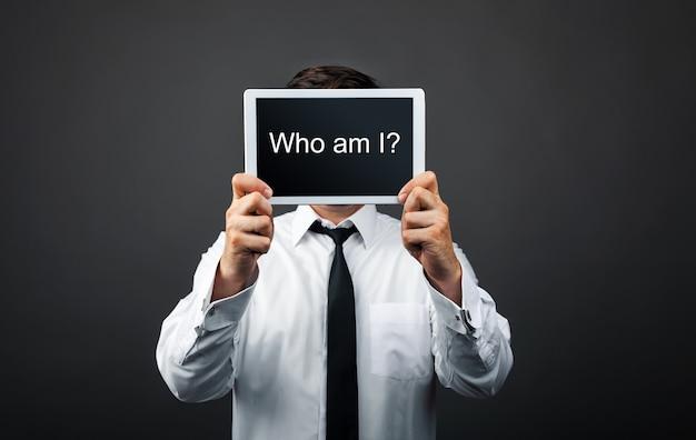 Biznesmen ukrywa twarz za znak zapytania