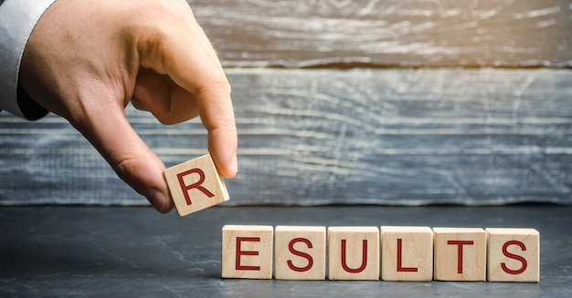 Biznesmen umieszcza bloki ze słowem wyniki.