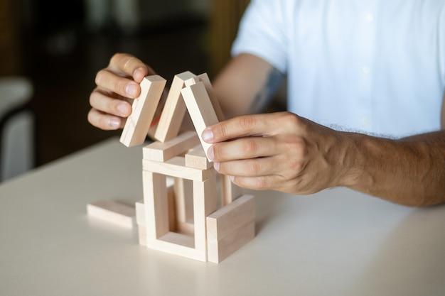 Biznesmen umieszcza drewniany klocek na koncepcji wieży kontrola ryzyka, planowanie i strategia w biznes.architekt projektuje dom
