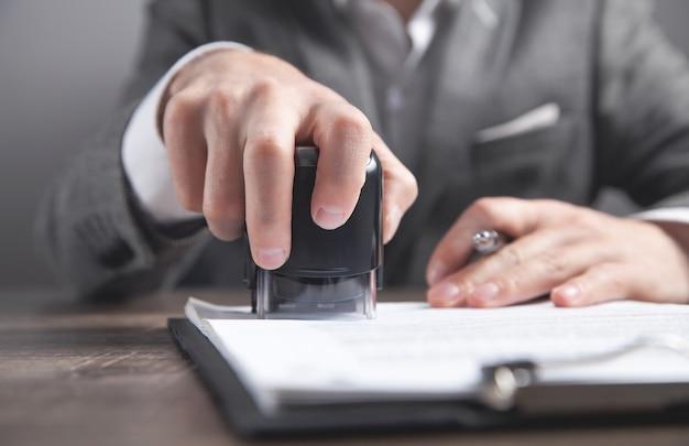 Biznesmen umieszcza pieczęć na dokumentach w biurze.