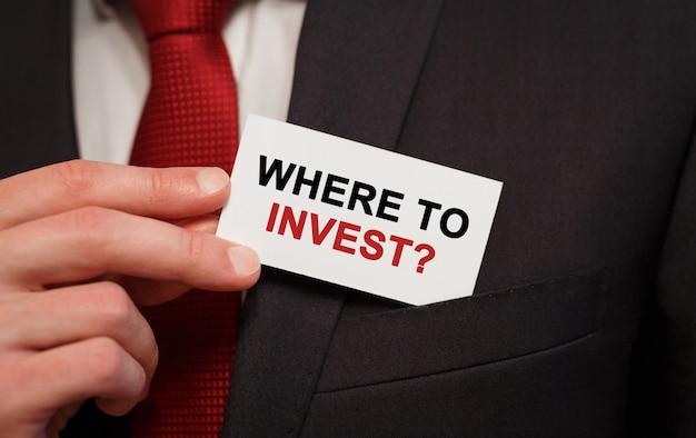 Biznesmen umieszczenie karty z tekstem gdzie inwestować w kieszeni