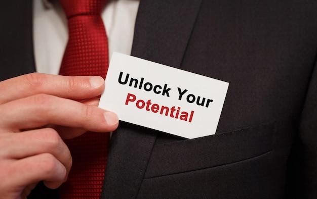 Biznesmen umieszczenie karty z tekstem odblokuj swój potencjał w kieszeni