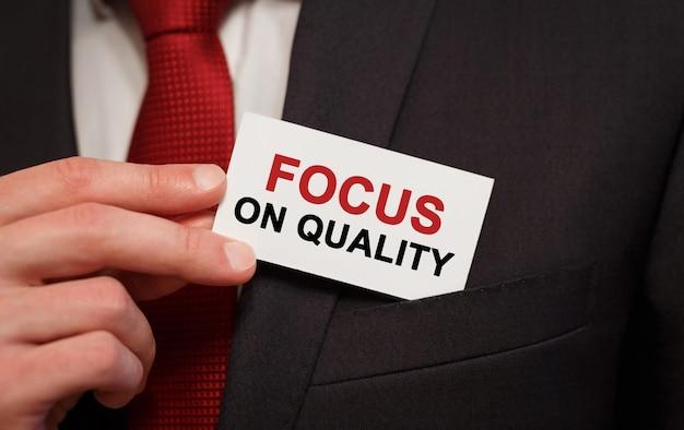Biznesmen umieszczenie karty z tekstem skoncentruj się na jakości w kieszeni