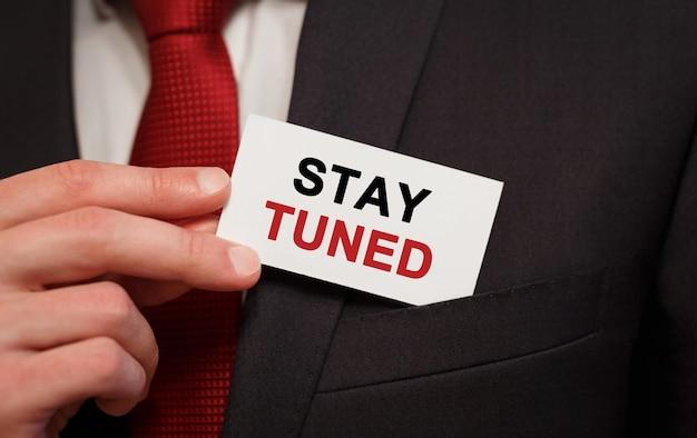 Biznesmen umieszczenie karty z tekstem stay tuned in the pocket