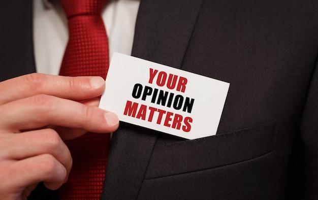 Biznesmen umieszczenie karty z tekstem twoja opinia ma znaczenie w kieszeni