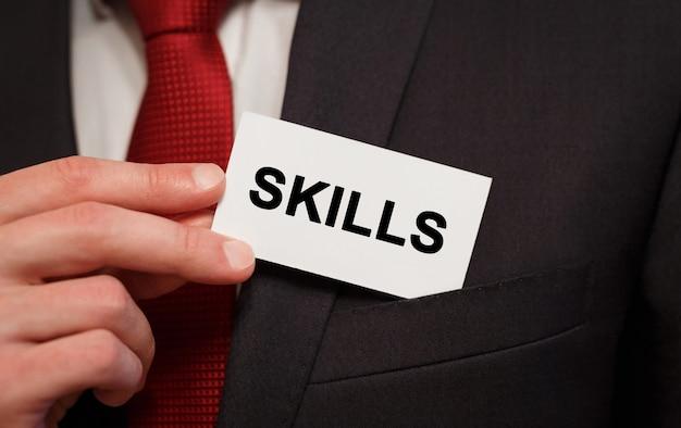 Biznesmen umieszczenie karty z tekstem umiejętności w kieszeni