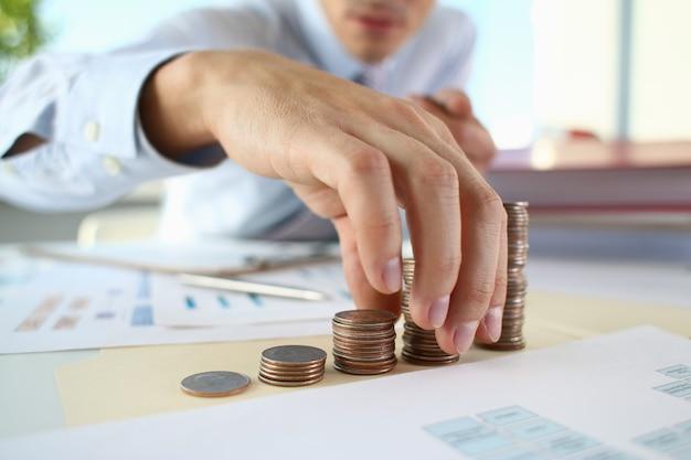 Biznesmen umieszczenie monet w stos na stole