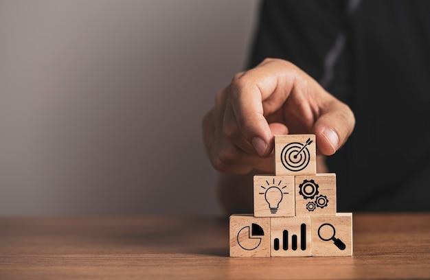 Biznesmen umieszczenie tablicy docelowej na innych ikonach dla konfiguracji celu osiągnięcia celu biznesowego.