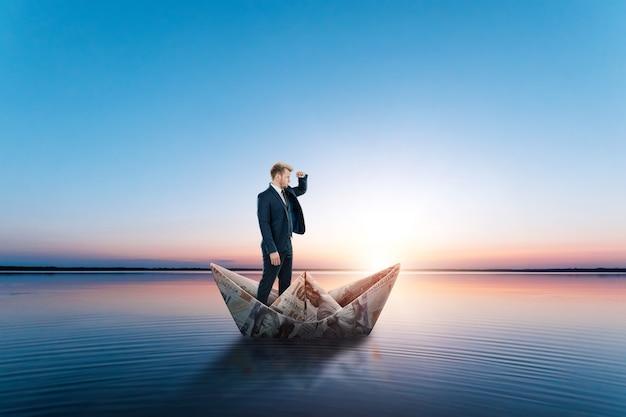 Biznesmen unosi się w papierowej łodzi wykonanej z banknotów dolarów. origami z pieniędzy, finansowy model biznesowy, droga do sukcesu, niezależność finansowa, kopia przestrzeń.