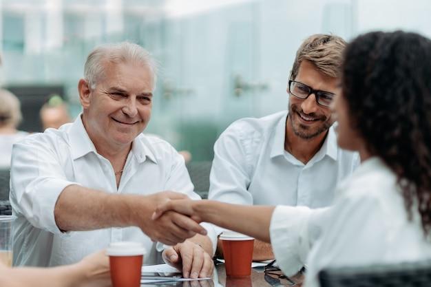 Biznesmen uścisk dłoni z bizneswoman siedzącą przy stole w kawiarni w centrum biznesowym