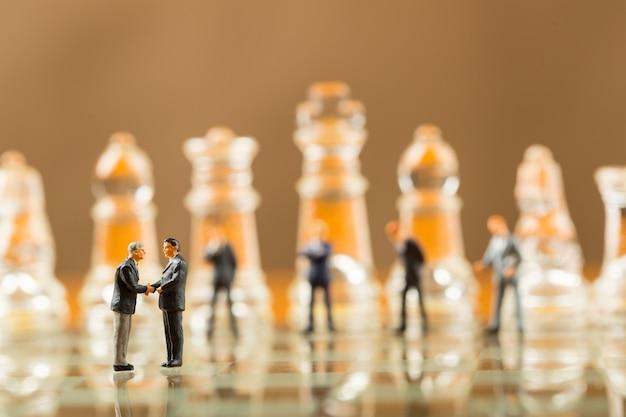 Biznesmen uścisnąć dłoń dla dobrego biznesu korporacyjnego z koncepcją gry w szachy.