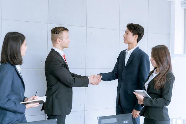 Biznesmen uścisnął sobie ręce, zgadzając się na sprzedaż dużych partii, która kończy cel planów marketingowych firmy