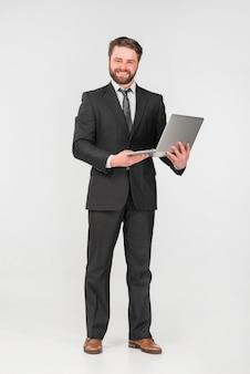 Biznesmen uśmiecha się i używa laptop