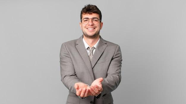 Biznesmen uśmiechający się radośnie z przyjaznym, pewnym siebie, pozytywnym spojrzeniem, oferujący i pokazujący przedmiot lub koncepcję