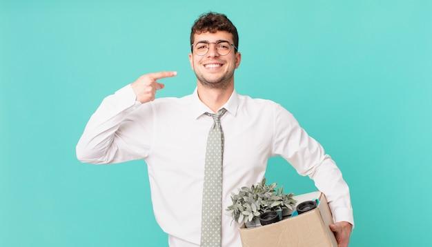 Biznesmen uśmiechnięty pewnie wskazując na własny szeroki uśmiech, pozytywne, zrelaksowane, zadowolone nastawienie. koncepcja zwolnienia