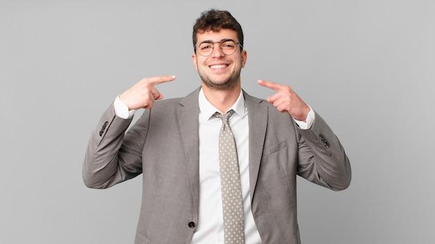 Biznesmen uśmiechnięty pewnie wskazujący na swój szeroki uśmiech, pozytywne, zrelaksowane, usatysfakcjonowane nastawienie