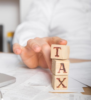 Biznesmen usuwa drewniane klocki słowem podatek. zmniejszenie lub restrukturyzacja długu. ogłoszenie upadłości. odmowa spłaty pożyczek i unieważnienie ich.