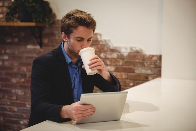 Biznesmen używa cyfrową pastylkę podczas gdy mieć kawę