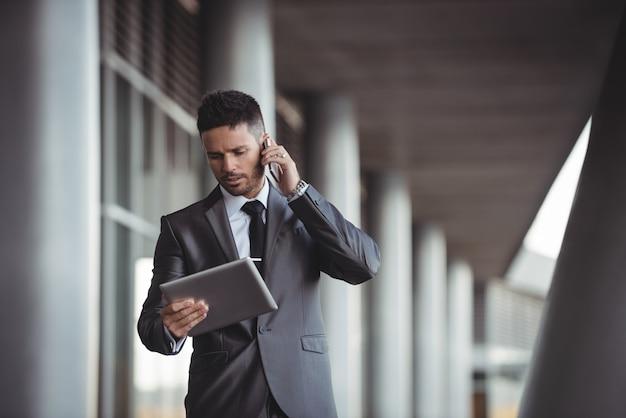 Biznesmen używa cyfrową pastylkę podczas gdy opowiadający na telefonie komórkowym
