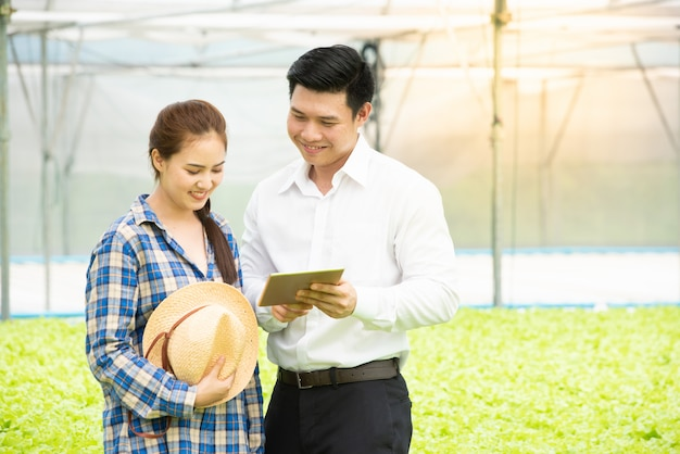 Biznesmen używa cyfrową pastylkę z 5g technologii systemu czeka jakością hydroponic organicznie warzywa gospodarstwo rolne z azjatykcim pięknym kobieta rolnikiem w szklarni, biznesowej opiece zdrowotnej i medycyny pojęciu ,.