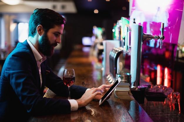 Biznesmen używa cyfrową pastylkę z wina szkłem na kontuarze