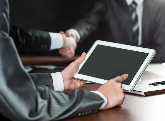 Biznesmen używa cyfrowego tabletu na odprawie w biurze
