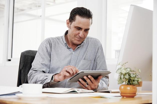 Biznesmen używa gadżety w pracy
