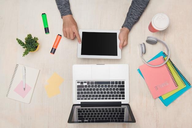 Biznesmen używa ipada lub tabletu przy jego biurowym stole. widok z góry, układ płaski.