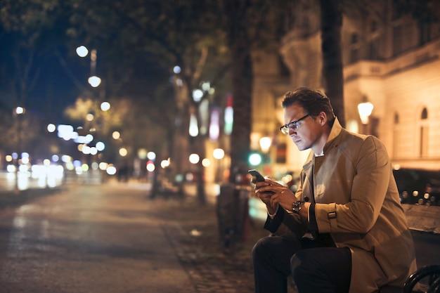 Biznesmen używa jego smartphone na ulicie