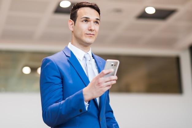 Biznesmen używa jego smartphone salowego