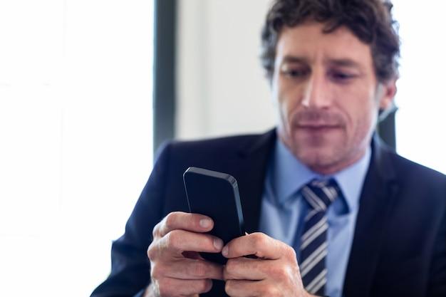 Biznesmen używa jego telefon komórkowego przy restauracją