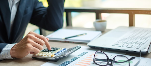 Biznesmen używa kalkulatora dla analizy maketing planu