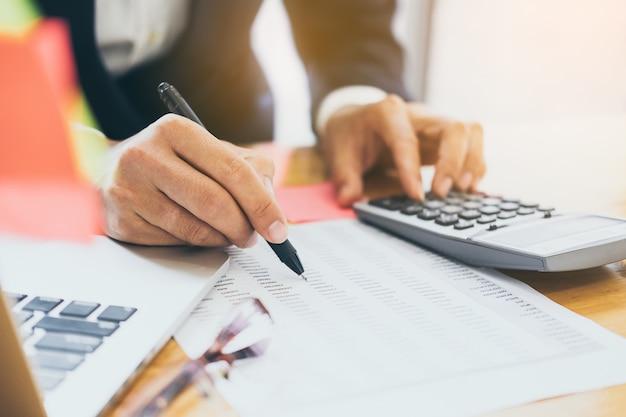 Biznesmen używa kalkulatora i laptopu