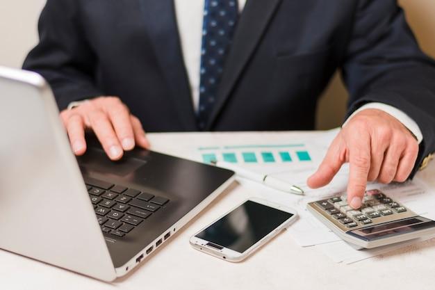 Biznesmen używa kalkulatora