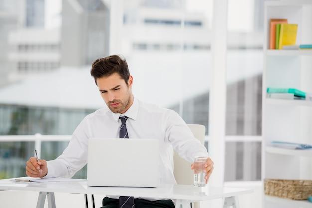 Biznesmen używa laptop i bierze notatki